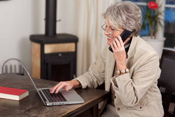 Side view of a smiling female pensioner using laptop and mobile phone at home